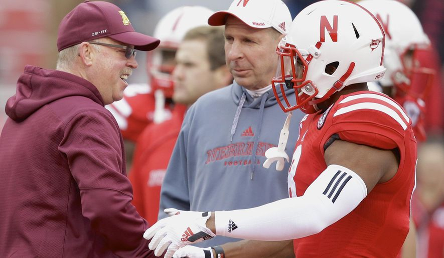 Minnesota head coach Jerry Kill, left, shakes the hand of Nebraska running back Ameer Abdulla, right, as Nebraska head coach Bo Pelini, center, looks on, before an NCAA college football game in Lincoln, Neb., Saturday, Nov. 22, 2014. (AP Photo/Nati Harnik)