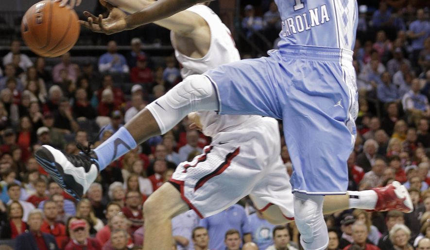 Davidson's Tyler Kalinoski, back, knocks the ball away from North Carolina's Theo Pinson, right, during the first half of an NCAA college basketball game in Charlotte, N.C., Saturday, Nov. 22, 2014. (AP Photo/Chuck Burton)
