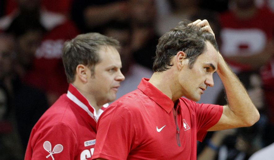 Switzerland's Roger Federer, right, holds his hair, followed by coach Severin Luthi, after losing to France's Gael Monfils during the Davis Cup final in Lille, northern France, Friday, Nov.21, 2014. Monfils won 6-1, 6-4, 6-3 to give France a 1-1 draw. (AP Photo/Christophe Ena)
