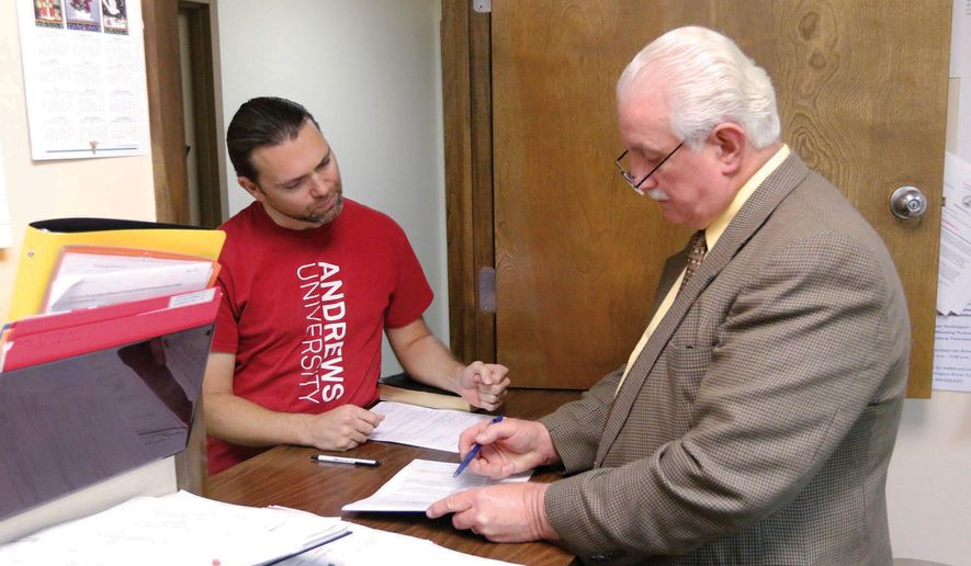 This Aug. 22, 2014 photo, Harrison Chief Magistrate Keith Marple goes over paperwork with Miracle Meadows School employee Timothy Arrington during his initial appearance in Salem, W.Va. The West Virginia boarding school for troubled youths was named in more than a dozen complaints of abuse and mistreatment over the past five years, one involving a student who allegedly volunteered a younger sibling to other residents for sex, according to an Associated Press review of state records. A teacher at the private Miracle Meadows school in Salem was accused in August of choking a young resident unconscious and handcuffing other residents in their rooms to restrain them. The teacher and the school's co-founder were arrested, the school was shut down and the Department of Health and Human Resources removed the school's 19 students. (AP Photo/The Exponent, Matt Harvey)