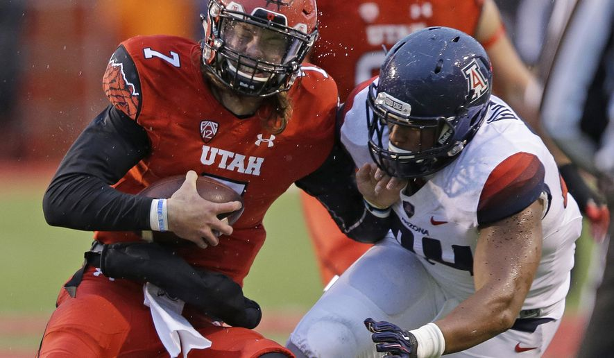 Utah quarterback Travis Wilson (7) is sacked by Arizona defensive lineman Reggie Gilbert (84) in the first half during an NCAA college football game Saturday, Nov. 22, 2014, in Salt Lake City. (AP Photo/Rick Bowmer)