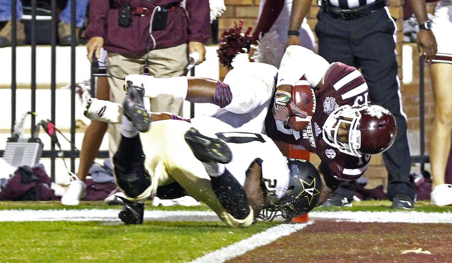 Mississippi State running back Josh Robinson (13) dives into the end zone for a touchdown over the attempted tackle by Vanderbilt defensive back Oren Burks (20) in the first half of an NCAA college football game Saturday, Nov. 22, 2014, in Starkville, Miss. (AP Photo/Rogelio V. Solis)