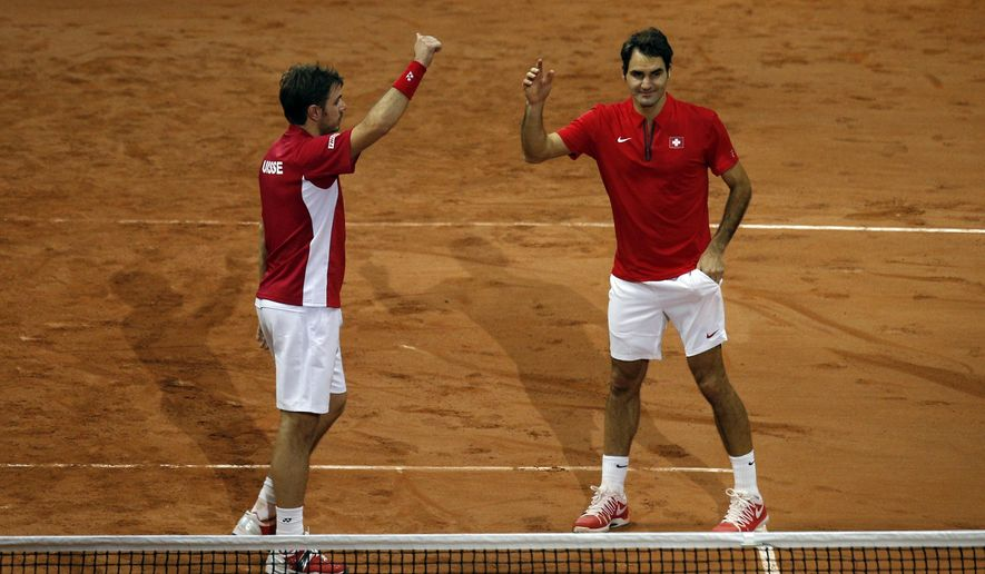 Switzerland's Roger Federer, right, and  compatriot Stanislas Wawrinka celebrate after   defeating France's Richard Gasquet and Julien Benneteau in their doubles match for the Davis Cup final in Lille, northern France, Saturday, Nov.22, 2014. The Swiss pair won 6-3, 7-5, 6-4 to give Switzerland a 2-1 lead. (AP Photo/Peter Dejong)