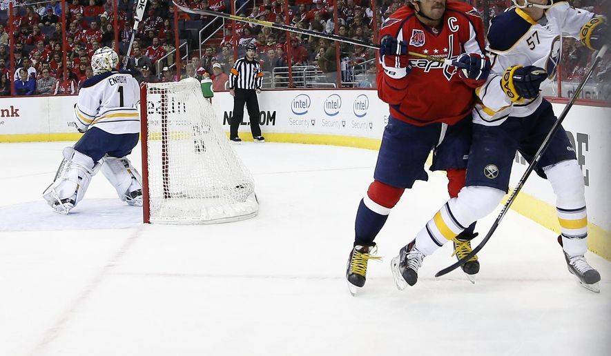 Washington Capitals left wing Alex Ovechkin (8), from Russia, boards Buffalo Sabres defenseman Tyler Myers (57) in the first period of an NHL hockey game, Saturday, Nov. 22, 2014, in Washington. (AP Photo/Alex Brandon)