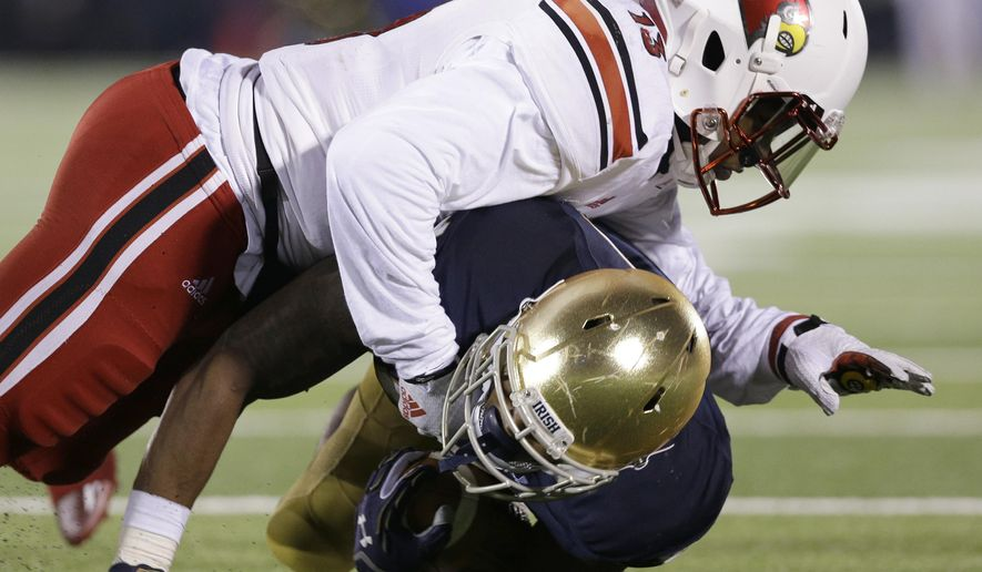 Louisville linebacker James Burgess, top, tackles Notre Dame running back Tarean Folston during the second half of an NCAA college football game in South Bend, Ind., Saturday, Nov. 22, 2014. Louisville won 31-28. (AP Photo/Nam Y. Huh)