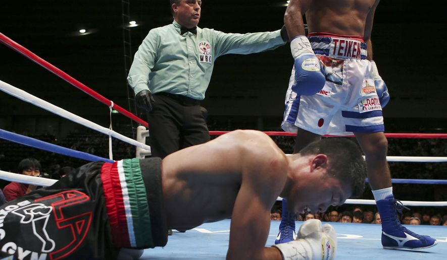 Rocky Fuentes of the Philippines lies down on ring after a knockdown by champion Roman Gonzalez of Nicaragua during their WBC flyweight title bout in Yokohama, Saturday, Nov. 22, 2014.  Gonzalez retained the title by technical knockout in the sixth round. (AP Photo/Koji Sasahara)