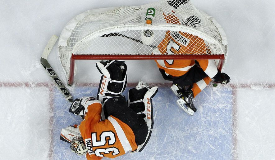 Philadelphia Flyers' Braydon Coburn (5) flies into the net after colliding with Steve Mason (35) during the first period of an NHL hockey game against the Columbus Blue Jackets, Saturday, Nov. 22, 2014, in Philadelphia. (AP Photo/Matt Slocum)