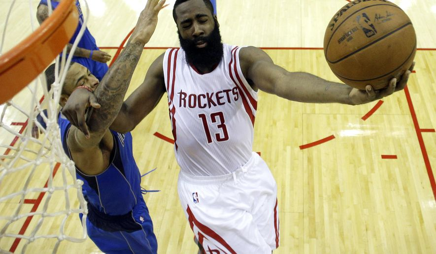 Houston Rockets' James Harden (13) goes up as Dallas Mavericks' Tyson Chandler defends during the first half of an NBA basketball game Saturday, Nov. 22, 2014, in Houston. (AP Photo/David J. Phillip)