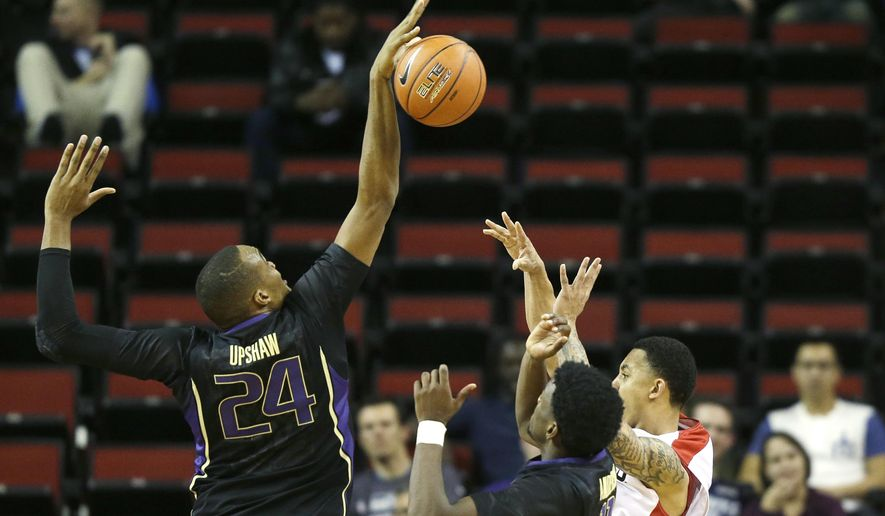 Washington's Robert Upshaw (24) blocks a shot by Seattle's Isiah Umipig, right, during the second half of an NCAA college basketball game, Friday, Nov. 21, 2014, in Seattle. Washington beat Seattle 63-48. (AP Photo/Ted S. Warren)