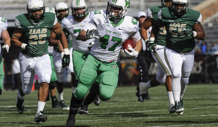 Marshall running back Devon Johnson (47) gains yardage with UAB linebacker Destin Challenger (25),and defensive tackle Jontavious Morris (55) in pursuit during the first quarter of an NCAA college football game, Saturday, Nov. 22, 2014, in Birmingham, Ala. (AP Photo/John Amis)