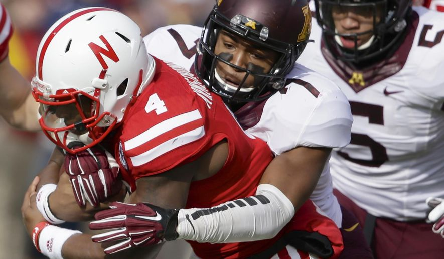 Nebraska quarterback Tommy Armstrong Jr. (4) is tackled by Minnesota defensive back Damarius Travis (7) in the first half of an NCAA college football game in Lincoln, Neb., Saturday, Nov. 22, 2014. Minnesota won 28-24. (AP Photo/Nati Harnik)