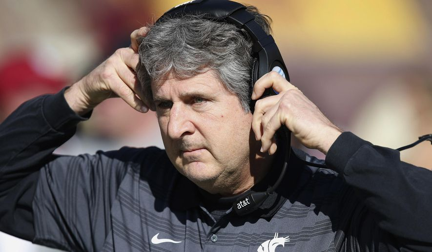 Washington State head coach Mike Leach adjusts his headset during the first half of an NCAA college football game against Arizona State, Saturday, Nov. 22, 2014, in Tempe, Ariz. (AP Photo/Ross D. Franklin)