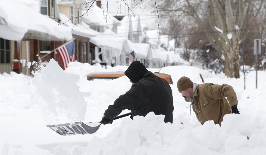 Mark Petrik and Dennis Smith dig out their south Buffalo driveway on Saturday, Nov. 22, 2014, in Buffalo, N.Y. Western New York continues to dig out from the heavy snow dropped by this week by lake-effect snowstorms. (AP Photo/Mike Groll)