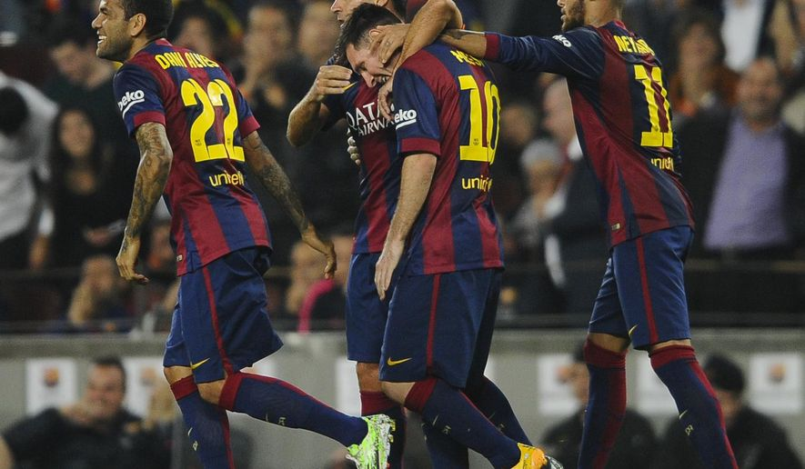 FC Barcelona's Lionel Messi, second right, from Argentina, celebrates scoring with his teammates Xavi Hernandez, center, and Neymar, from Brazil, right, against Sevilla during a Spanish La Liga soccer match at the Camp Nou stadium in Barcelona, Spain, Saturday, Nov. 22, 2014. (AP Photo/Manu Fernandez)