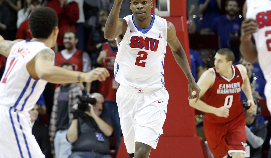 SMU center Yanick Moreira (2) throws up a finger in celebration, after slam dunking a ball during the first half of an NCAA college basketball against Eastern Washington Saturday, Nov. 22, 2014, in Dallas. (AP Photo/John F. Rhodes)