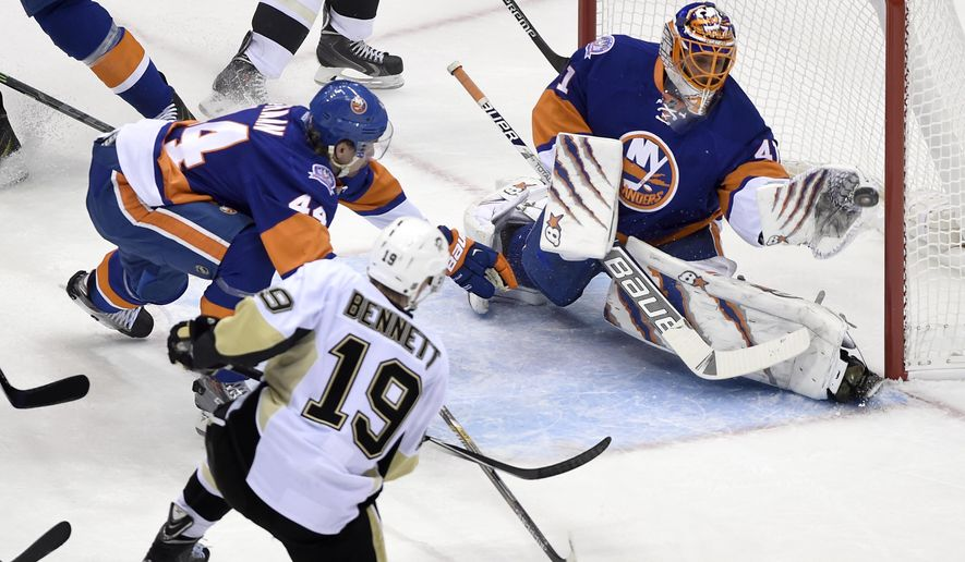 New York Islanders goalie Jaroslav Halak (41) stops a shot on goal by Pittsburgh Penguins right wing Beau Bennett (19), as New York Islanders defenseman Calvin de Haan (44) defends in the first period of an NHL hockey game at Nassau Coliseum on Saturday, Nov. 22, 2014, in Uniondale, N.Y. (AP Photo/Kathy Kmonicek)
