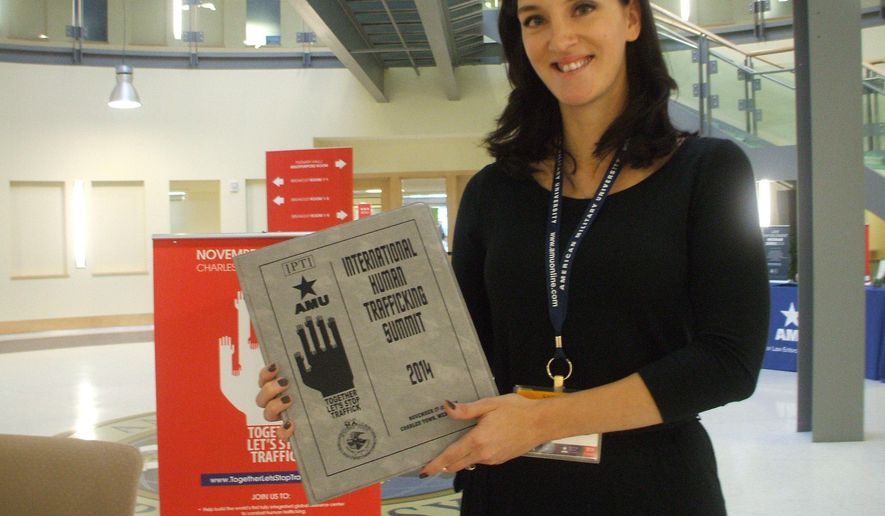 ADVANCE FOR SUNDAY NOV. 23 AND THEREAFTER This Monday Nov. 17, 2014 shows Shepherdstown resident Dr. Danielle Johnson displays a booklet at an international summit in Charles Town, W.Va.  Johnson got interested in human rights abuses after spending time in Bosnia and now works with Polaris, a national, nonprofit group that fights human trafficking aimed at better combating human trafficking globally. (AP Photo/The Journal, Jenni Vincent)