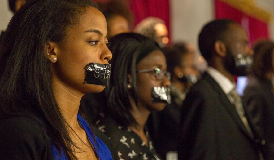 FILE - In this March 24, 2014 file photo, members of the Nashville Student Organizing Committee stage a silent protest in the gallery of the House chamber in Nashville, Tenn.. The group opposes a state law that prevents student IDs to be used to vote in Tennessee.   A new report by the Government Accountability Office found that states, including Tennessee, which toughened their voter ID laws saw steeper drops in election turnout than those that did not. While there were few reports of voting problems in Tennessee following the Nov. 4 general election, voter advocates say the report justifies the need to examine the effects of the voter ID law in Tennessee, one of 33 states to enact laws obligating voters to show a photo ID at the polls. (AP Photo/Erik Schelzig)