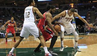 Washington Wizards forward Nene Hilario, center, is defended by Milwaukee Bucks forward Jabari Parker, left, and guard Giannis Antetokounmpo, right, during the first half of an NBA basketball game Saturday, Nov. 22, 2014, in Milwaukee. (AP Photo/Darren Hauck)