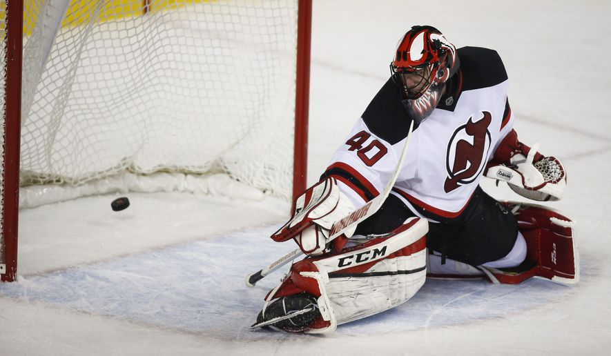 New Jersey Devils goalie Scott Clemmensen looks back at a goal by Calgary Flames' Jiri Hudler, from the Czech Republic, during the shootout in an NHL hockey game in Calgary, Alberta, Saturday, Nov. 22, 2014. The Flames won 5-4. (AP Photo/The Canadian Press, Jeff McIntosh)