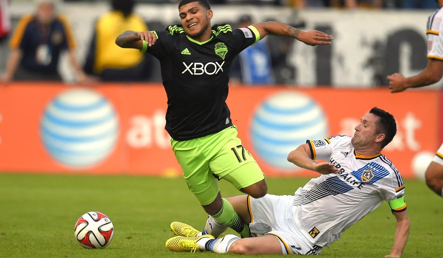 Seattle Sounders FC defender Deindre Yedlin, left, falls as Los Angeles Galaxy forward Robbie Keane goes after the ball during the first half of a Major League Soccer playoff game, Sunday, Nov. 23, 2014, in Carson, Calif. (AP Photo/Mark J. Terrill)
