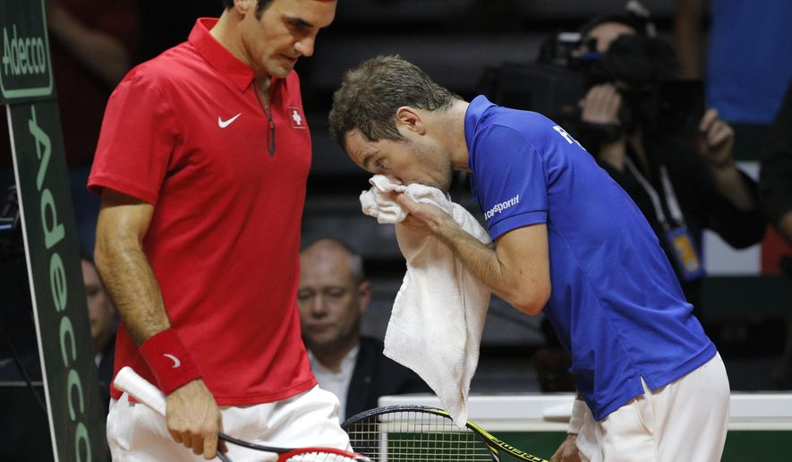 Switzerland's Roger Federer, left, and France's Richard Gasquet walk back to their seat during a break during the Davis Cup final match in Lille, northern France, Sunday, Nov.23, 2014. (AP Photo/Christophe Ena)