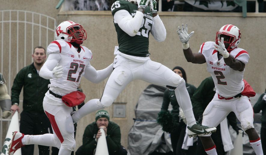 Michigan State's Keith Mumphery (25) can't hang on to a pass in the end zone between Rutgers' Delon Stephenson (27) and Gareef Glashen (2) during the second quarter of an NCAA college football game, Saturday, Nov. 22, 2014, in East Lansing, Mich. Michigan State won 45-3. (AP Photo/Al Goldis)