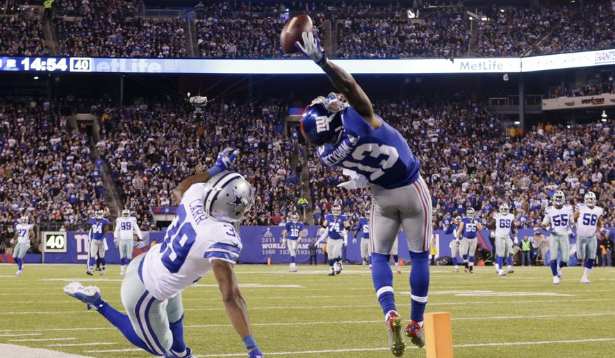 New York Giants wide receiver Odell Beckham Jr. (13) makes a one-handed catch for a touchdown against Dallas Cowboys cornerback Brandon Carr (39) in the second quarter of an NFL football game, Sunday, Nov. 23, 2014, in East Rutherford, N.J. (AP Photo/Julio Cortez)