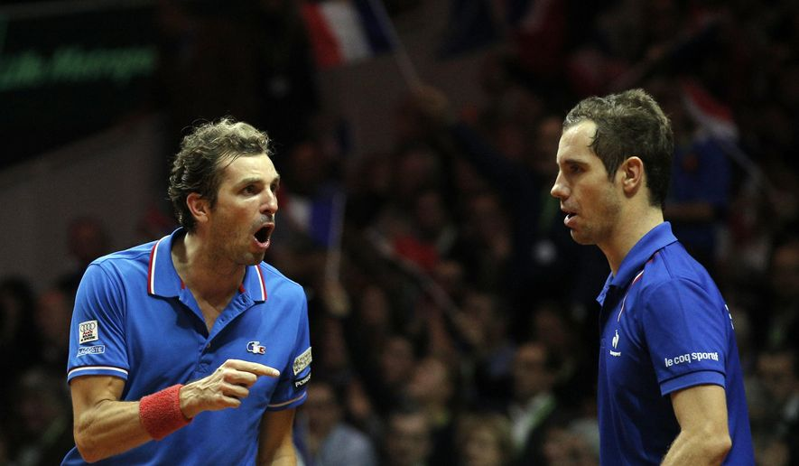 France's Julien Benneteau, left, points to Richard Gasquet as they plays Switzerland's Roger Federer and Stanislas Wawrinka  during their doubles match for the Davis Cup final in Lille, northern France, Saturday, Nov.22, 2014. (AP Photo/Christophe Ena)