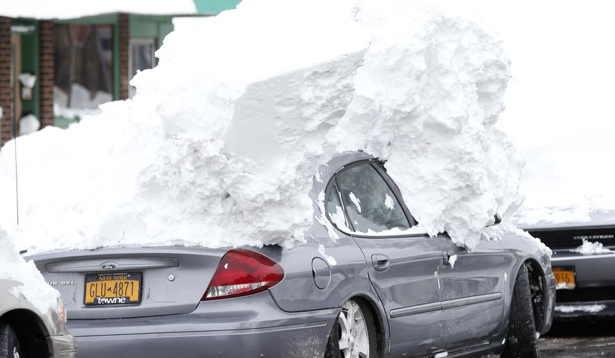 A car is weighed down by heavy snow in the south Buffalo area on Saturday, Nov. 22, 2014, in Buffalo, N.Y. Western New York continues to dig out from the heavy snow dropped by this week by lake-effect snowstorms. (AP Photo/Mike Groll)
