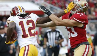 Washington Redskins' Andre Roberts (12) stiff arms San Francisco 49ers' Craig Dahl during the first quarter of an NFL football game in Santa Clara, Calif., Sunday, Nov. 23, 2014. (AP Photo/Tony Avelar)