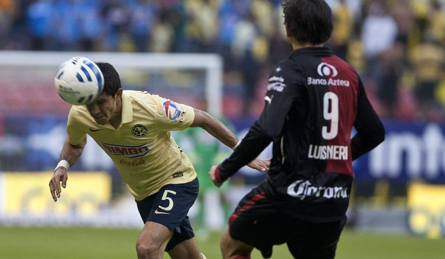 America's Jesus Molina, left, heads for the ball next to Luis Caballero of Atlas during a Mexican soccer league match in Mexico City, Saturday, Nov. 22, 2014. (AP Photo/Christian Palma)