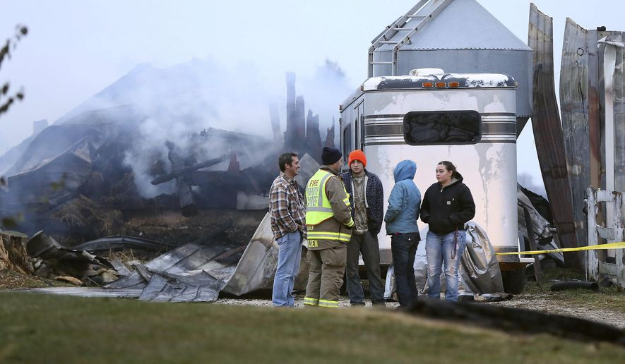 An official stands with Tyson Bauman, left, one of the owners of Valley View Acres, and others, near the scene where more than 30 horses died in a stable fire in Crystal Lake, Ill.. Sunday, Nov. 23, 2014. As firefighters arrived before midnight Saturday, the stable's owners were running around the complex looking for ways to lead horses to safety, Crystal Lake Fire Rescue Chief Paul Deraedt said in a phone interview. (AP Photo/Northwest Herald, Joe Shuman)