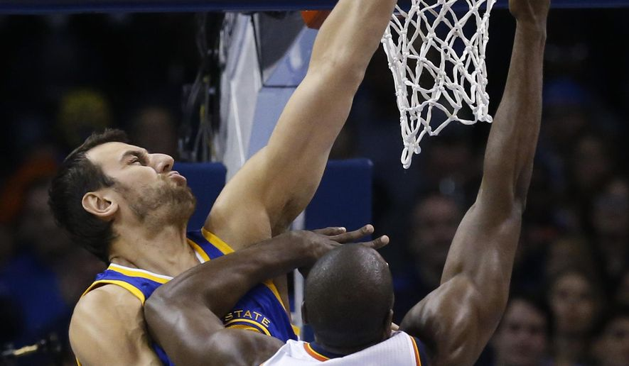 Golden State Warriors center Andrew Bogut, left, blocks a shot by Oklahoma City Thunder forward Serge Ibaka (9) in the first quarter of an NBA basketball game in Oklahoma City, Sunday, Nov. 23, 2014. (AP Photo/Sue Ogrocki)