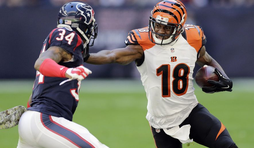 Cincinnati Bengals' A.J. Green (18) tries to avoid Houston Texans' A.J. Bouye (34) as he runs with the ball during the first quarter of an NFL football game, Sunday, Nov. 23, 2014, in Houston. (AP Photo/Patric Schneider)