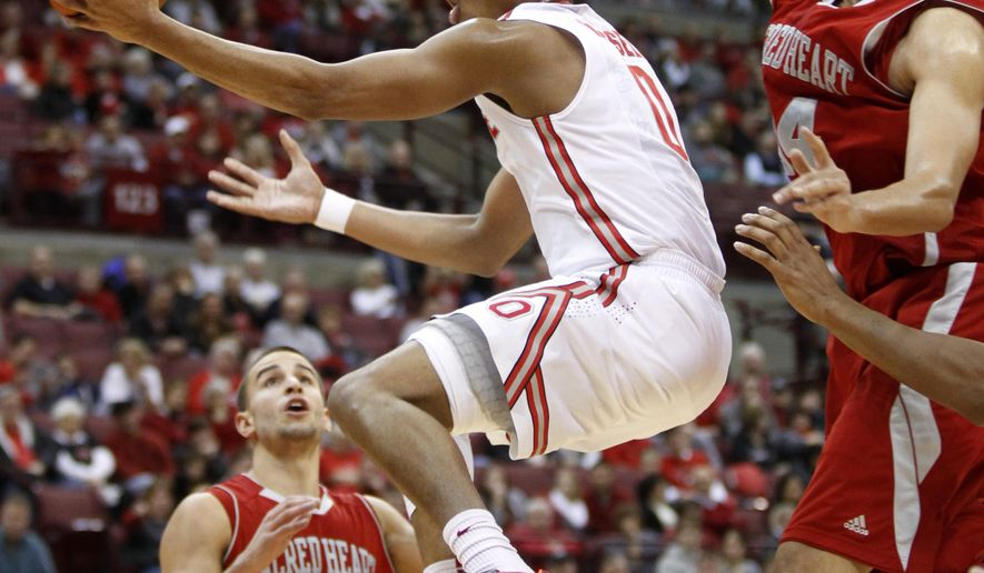 Ohio State's D'Angelo Russell (0) goes up for shot between Sacred Heart's Steve Glowiak (31) and Tevin Falzon (34) during the first half of an NCAA college basketball game in Columbus, Ohio, Sunday, Nov. 23, 2014. (AP Photo/Paul Vernon)
