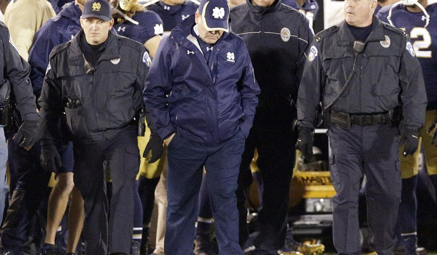Notre Dame head coach Brian Kelly, center, looks down as he walks on the field after Notre Dame's 31-28 loss to Louisville in an NCAA college football game in South Bend, Ind., Saturday, Nov. 22, 2014. (AP Photo/Nam Y. Huh)