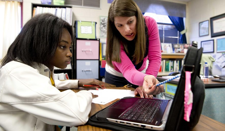 In this Nov. 20, 2014 photo, eight grader Aklya Thomas and teacher Faren Fransworth use a digital textbook to during a math class at Burney Harris Lyons Middle School in Athens Ga. Georgia schools will use only digital textbooks within the next six years under a proposal one state lawmaker has planned for the 2015 session. (AP Photo/John Bazemore)