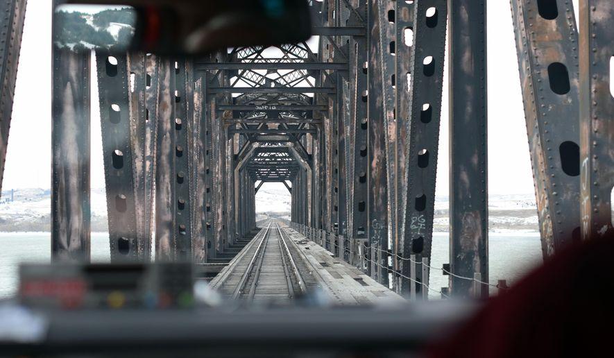 In this Nov. 11, 2014 photo, Lynn Kennison drives the hi-rail truck across a rail bridge near Chamberlain, S.D. (AP Photo/James Nord)
