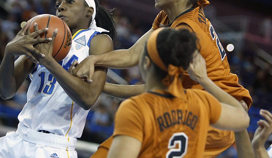 UCLA center Luiana Livulo (13) pulls down a loose ball in front of Texas guard Brianna Taylor, top right, in the first half of an NCAA college basketball game in Los Angeles, Sunday, Nov. 23, 2014. (AP Photo/Christine Cotter)