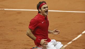 Switzerland's Roger Federer falls to the clay after defeating France's Richard Gasquet and winning the Davis Cup final between France and Switzerland at Stade Pierre Mauroy in Lille, northern France, Sunday, Nov. 23, 2014. (AP Photo/Peter Dejong)