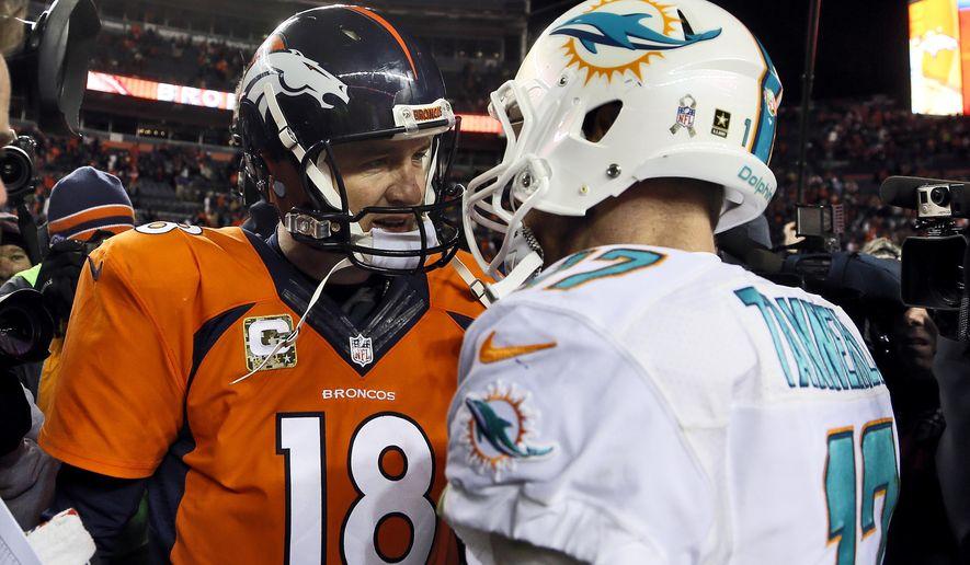 Denver Broncos quarterback Peyton Manning (18) greets Miami Dolphins quarterback Ryan Tannehill (17) after an NFL football game, Sunday, Nov. 23, 2014, in Denver. The Broncos won 39-36. (AP Photo/Joe Mahoney)