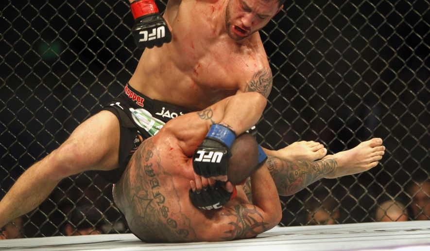 Frankie Edgar, top, strikes Cub Swanson in a featherweight mixed martial arts bout during the UFC Fight Night at the Frank Erwin Center in Austin, Texas, Sunday, Nov. 23, 2014. (AP Photo/Michael Thomas)