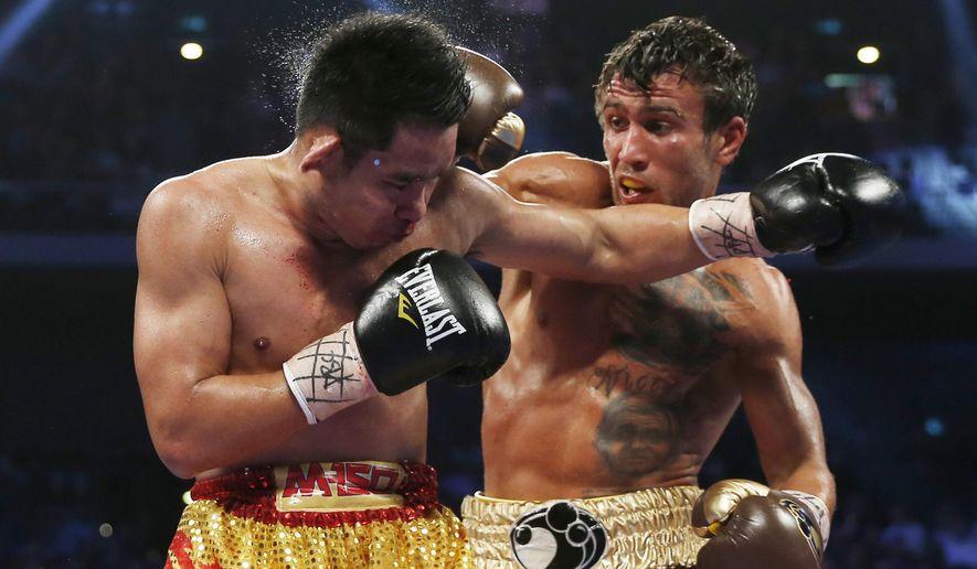 Chonlatarn Piriyapinyo, left, of Thailand gets a punch from Vasyl Lomachenko of Ukraine during their WBO world featherweight boxing title match at the Venetian Macao in Macau, Sunday, Nov. 23, 2014. (AP Photo/Kin Cheung)