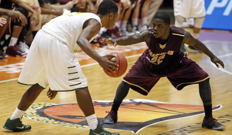 George Mason guard Marquise Moore, left, dribbles against College of Charleston guard Anthony Stitt during a NCAA college basketball game in San Juan, Puerto Rico, Sunday, Nov. 23, 2014. (AP Photo/Ricardo Arduengo)