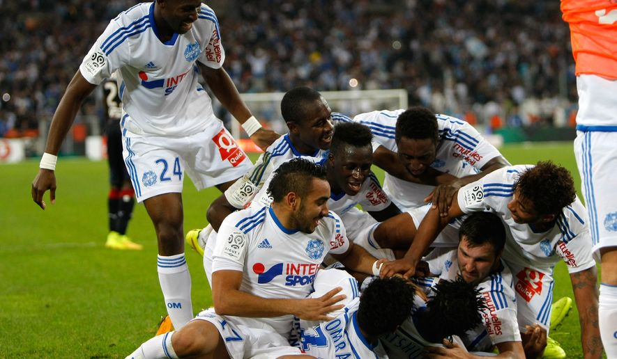 Marseille's players celebrate after Marseille's Belgian forward Michy Batshuayi, second left bottom, scored against Bordeaux, during their League One soccer match, at the Velodrome Stadium, in Marseille, southern France, Sunday, Nov. 23, 2014. (AP Photo/Claude Paris)