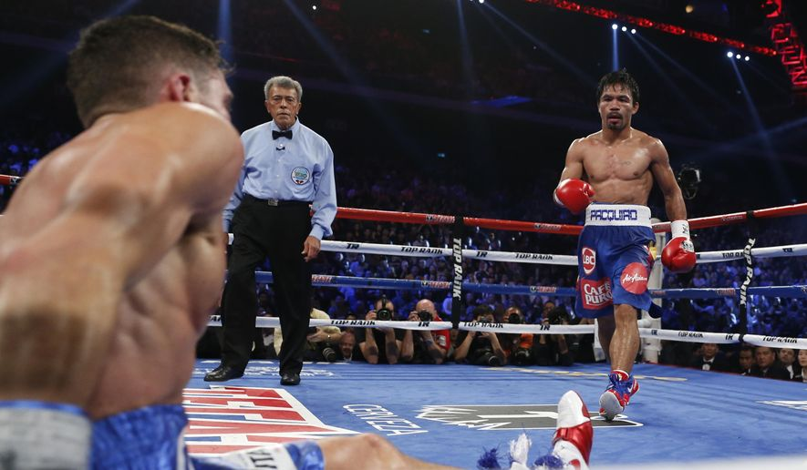WBO junior welterweight champion Chris Algieri of the United States sits on the mat after being knocked down by WBO welterweight champion Manny Pacquiao of the Philippines during their WBO welterweight boxing match at the Venetian Macao in Macau, Sunday, Nov. 23, 2014. (AP Photo/Kin Cheung)