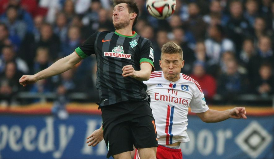 Bremen's  Izet Hajrovic , left, challenges for the ball with  Hamburg's Kentin Mahe during the German first division Bundesliga soccer match between SV Weder Bremen and Hamburger SV in Bremen, northern Germany, Sunday Nov. 23, 2014.  (AP Photo/dpa, Axel Heimken/