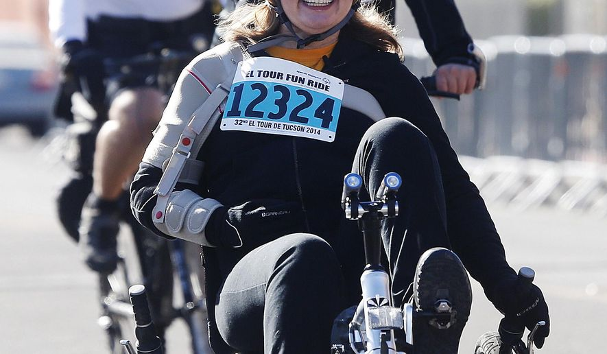 Former U.S. Rep. Gabrielle Giffords arrives back at the finish line for the 12-mile fun ride at the Special Olympics El Tour de Tucson bicycle race on Saturday, Nov. 22, 2014, in Tucson.  (AP Photo/Arizona Daily Star, Mike Christy)  ALL LOCAL TELEVISION OUT; PAC-12 OUT; MANDATORY CREDIT
