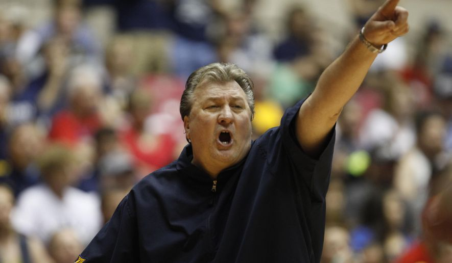 West Virginia basketball coach Bob Huggins yells out instructions to his players during a NCAA college basketball game against UConn in San Juan, Puerto Rico, Sunday, Nov. 23, 2014. (AP Photo/Ricardo Arduengo)